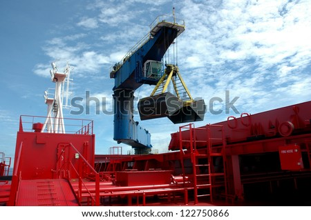 a heavy equipment from the pontoon boat was filling the  coal into a tanker - stock photo