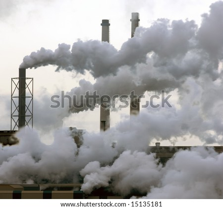 A heavy industry production plant with steam and fumes from various exhausts - stock photo