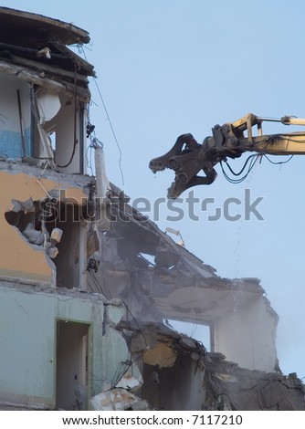 a heavy machine knocking down an old building