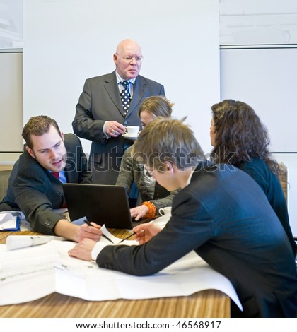 A hectic meeting, with five people working frantically on a design - stock photo