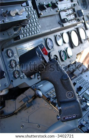 A helicopter cockpit with the control stick in the foreground and the instruments and switches in the background. - stock photo