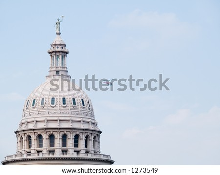 A helicopter flys by the Texas State Capitol building in Austin, Texas. - stock photo