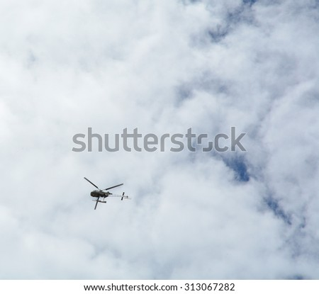 A helicopter on a background of cloud sky. - stock photo