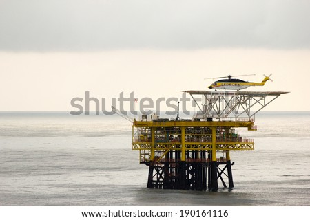 A helicopter on top of a offshore oil-platform transporting roughnecks to nearby rigs - stock photo