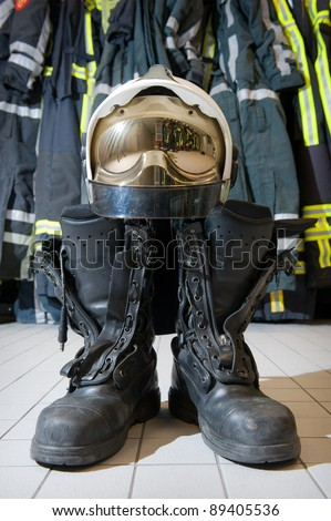 A helmet and boots on the floor in a fire station ready to be used by firefighters - stock photo