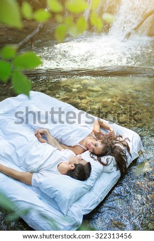 A hidden place. Sleeping couple in deep forest lies on airbed. Waterfall on back - stock photo