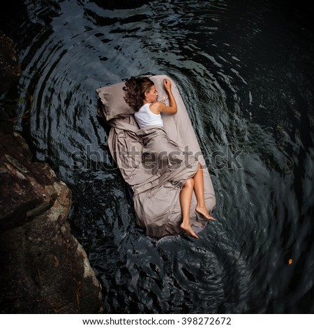 A hidden place. Sleeping woman in deep forest lies on airbed - stock photo
