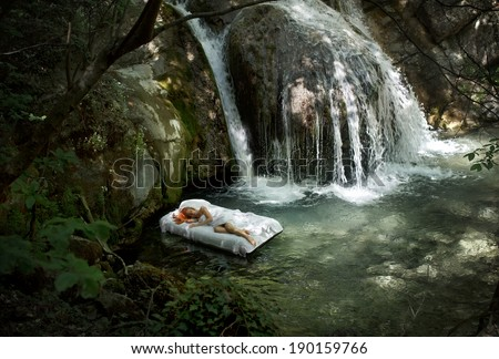 a hidden place. Sleeping woman in deep forest with waterfall on back - stock photo