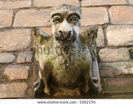 A hideous gargoyle stares down from an old roof in York, England. - stock photo