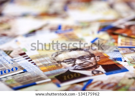 A high angle macro shot view of a very large amount of 100 NIS (New Israeli Shekel) money notes spread in a messy manner. Very shallow depth of field. - stock photo