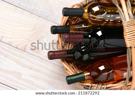 A high angle shot of wine bottles in a basket on a whitewashed wood farmhouse style kitchen table. Horizontal format with copy space.