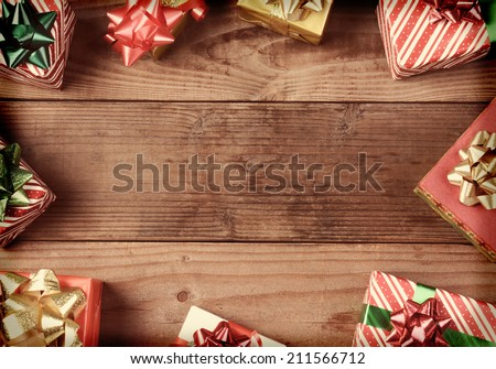 A high angle view of a group of Christmas presents on a rustic wooden floor. The presents are scattered around the edges of the frame leaving an empty middle for your object or copy. Instagram Look. - stock photo