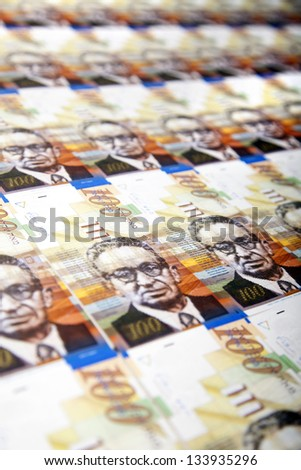 A high angle view of a very large amount of 100 NIS (New Israeli Shekel) money notes, depicted diagonally. - stock photo