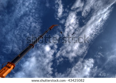 a high dynamic range image of an action sports thrill seeker after jumping from a bungee platform. - stock photo