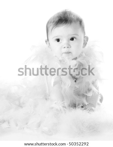A high-key black and white image of a beautiful baby girl wrapped in feathery boas.