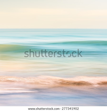 A high-key seascape featuring ocean waves with blurred panning motion.  Image displays subtle cross-processing and light, pastel colors. - stock photo