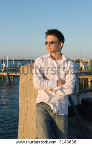A high school boy standing in the seabreeze watching a Florida sunset leaning against a piling at a marina. - stock photo