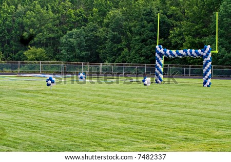 A High School football field with goal posts decorated with balloons. The field decorations are preparations for a graduation ceremony.