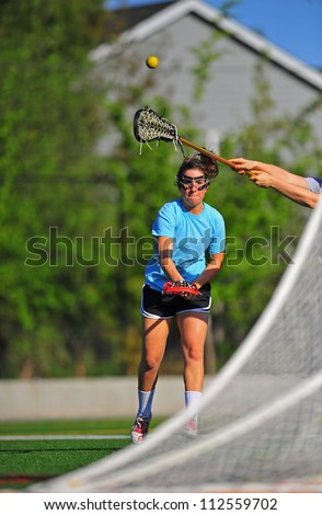 A high school girls lacrosse player takes a shot on goal as a defender stick her stick up to try and block the shot. - stock photo