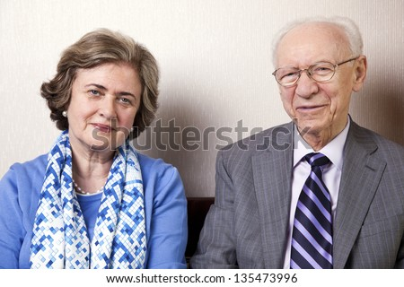 A high society senior couple (he's in his 80's, she's in her late 60's) sitting on a sofa looking at the camera. Medium close up. - stock photo