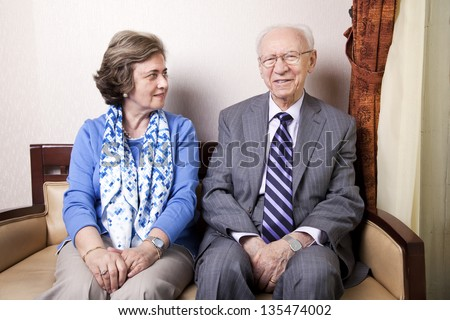 A high society senior couple (his 80's, her late 60's) sitting on a sofa. She's looking away to the right side of the frame, and he's looking straight to the camera, with a slight smile on his face. - stock photo