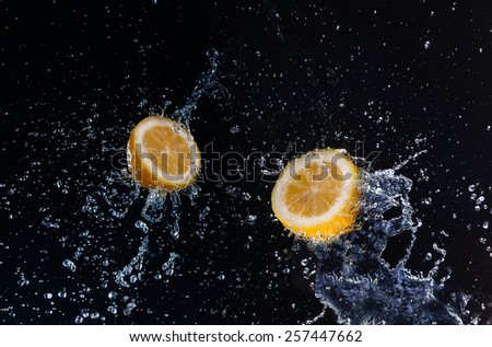 A high-speed shot of a lemon with splashing water, on a black background. - stock photo