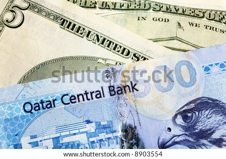 A high-value Qatari 500 riyal banknote, on top of US currency notes. Concern over the impact of the falling dollar may lead Qatar (and other oil states) to move or end the dollar peg.