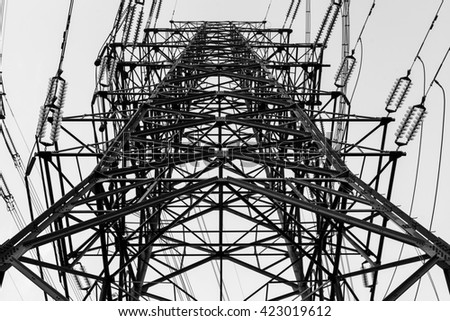 a high voltage power pylons against blue sky and sun rays - stock photo