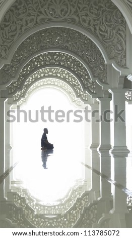 A highkey image of a Muslim prays. - stock photo