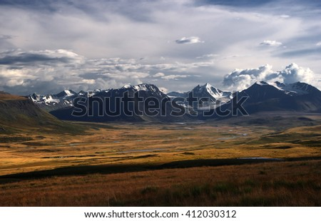 A highland river valley with yellow grass on a background of snow covered mountains and glaciers under clouds and blue sky, Plateau Ukok, Altai mountains, Siberia, Russia - stock photo
