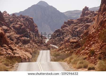 A highway rolling through red rock canyons in Nevada - stock photo