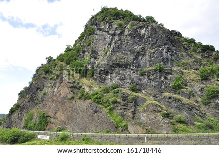 A highway that travels along a jagged and rocky mountain side. - stock photo
