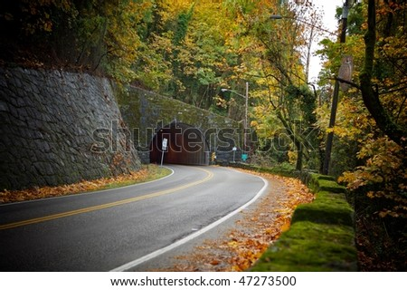 A highway tunnel cutting through a mountain - stock photo
