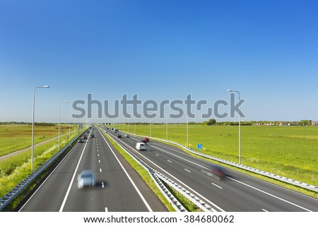 A highway with traffic through grassy fields on a bright and sunny day in The Netherlands. - stock photo
