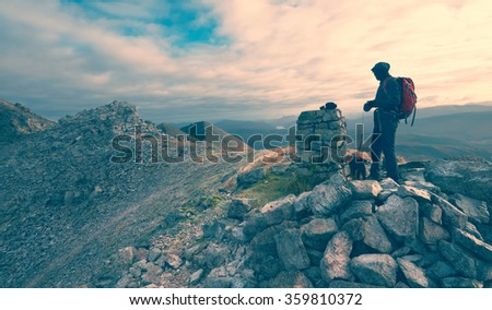 A hiker and their dog on a mountain summit. This image has added grain and styling. - stock photo