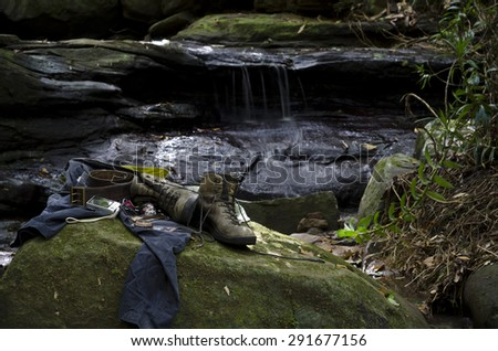 A hiker's boots and personal belongings on a moss covered rock by a forest creek. Hiking gear consists of shirt, dark cargo pants, worn out hiking boots, headlamp, compass, leather belt and knife.  - stock photo