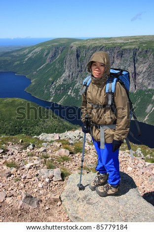 A hiker standing on Gros Morne Mountain with Ten Mile Pond below. Gros Morne National Park, Newfoundland, Canada. - stock photo