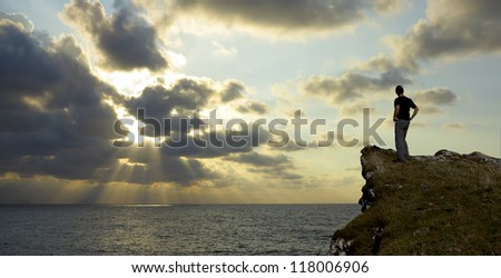 A hiker watch the sunset on the coast. - stock photo