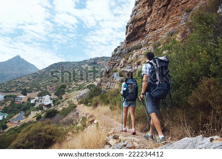 A hiking couple walking along the trail of the bottom of the mountain with copyspace - stock photo