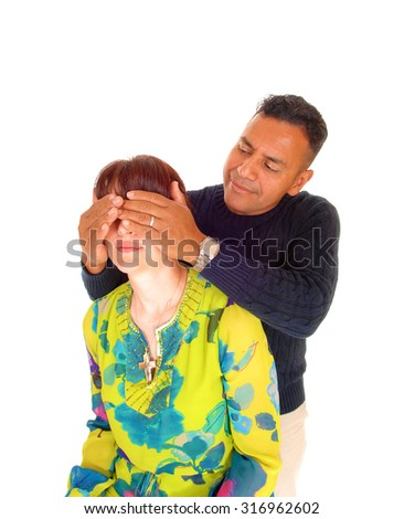 A Hispanic man, standing behind his wife and holding his hands over her eye's, isolated for white background.  - stock photo