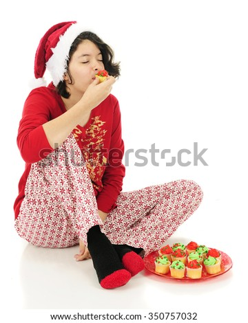 A Hispanic teen girl loving the mini cupcake that she's eating in her Christmas pajamas.  On a white background.