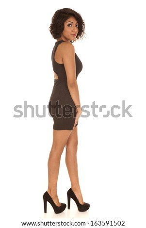 a Hispanic woman standing in her little black dress and heels. - stock photo