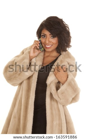 A Hispanic woman talking on her phone in her fur coat and dress.
