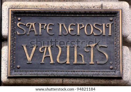 A historic heavy brass sign announcing safe deposit vaults at a former bank.