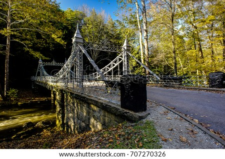 A historic iron suspension bridge crosses Mill Creek in Mill Creek Park in Youngstown, Ohio on a warm and sunny autumn afternoon.