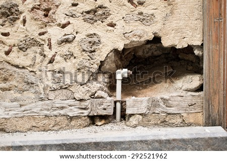 A hole in a stone wall with a water pipe - stock photo