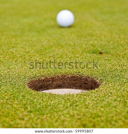 A hole over golf ball on green. Shallow depth of field. Focus on the hole. - stock photo