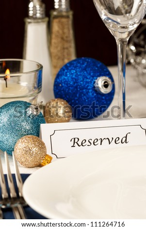 A holiday table setting with an empty plate providing copy space is decorated with blue and gold ornaments and a placard showing a reserved place - stock photo