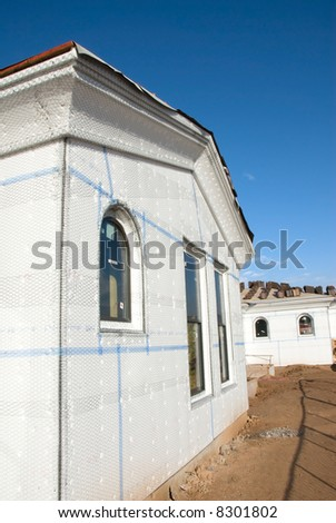 A home at a new construction site is layered with insulating foam before the stucco is added.  Ideal for new home construction advertising and other home construction promotional inferences. - stock photo