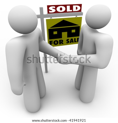 A home buyer and seller shake hands in front of a for sale sign that is marked Sold. - stock photo